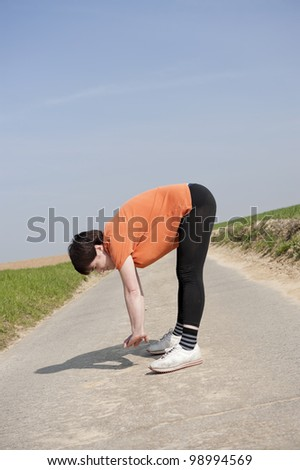 Mid adult jogging woman doing stretching - stock photo