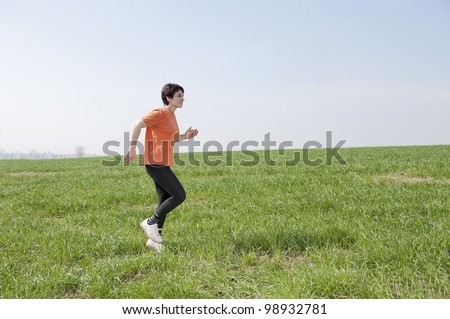 mid adult jogging woman  in the fields - stock photo