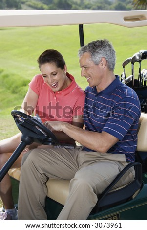 Mid-adult male and female in golf cart pointing at score card. - stock photo