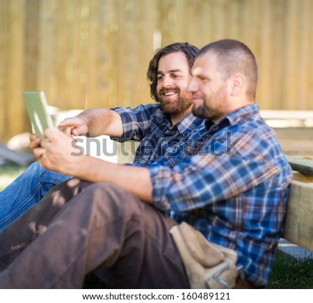 Mid adult male carpenter holding digital tablet while coworker pointing at it