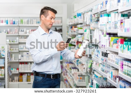 Mid adult male customer scanning product through mobile phone in pharmacy - stock photo