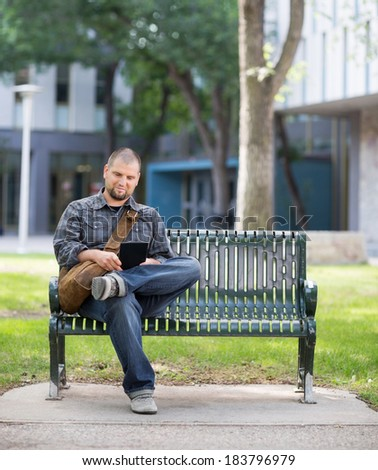 Mid adult male university student using digital tablet while sitting on bench at campus - stock photo