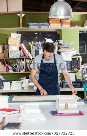 Mid adult male worker working at table in paper factory - stock photo