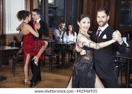 Mid Adult Man And Woman Performing Tango In Restaurant