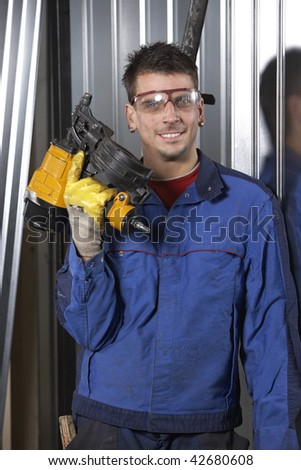 mid adult man at workshop looking at camera and holding a nail gun