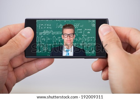 Mid adult man attending online math's lecture on smartphone - stock photo
