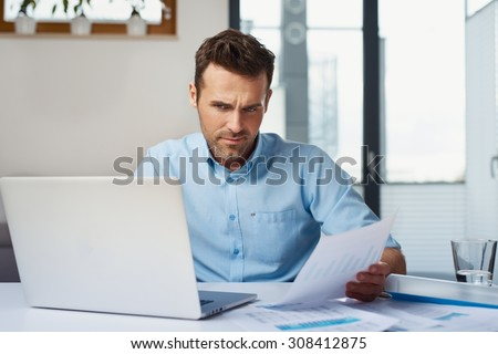Mid adult man calculating home finances on laptop at home - stock photo