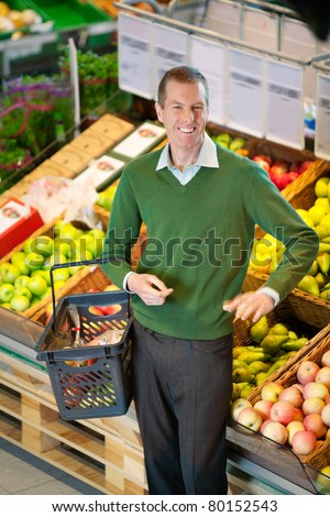 Mid adult man carrying shopping basket and looking at camera while shopping in fruit store - stock photo