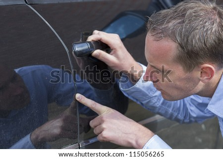 Mid adult man checking his car for scratches and dents. Horizontal shot. - stock photo