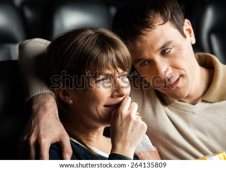 Mid adult man comforting woman crying while watching movie in cinema theater - stock photo