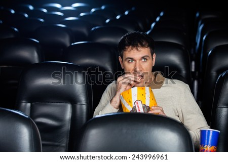 Mid adult man eating popcorn while watching movie in cinema theater - stock photo