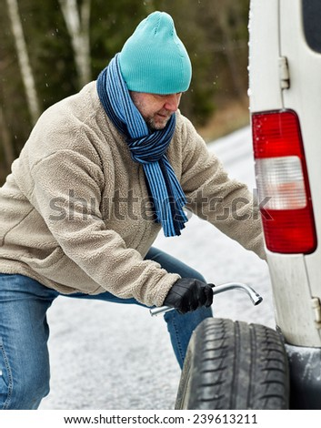 Mid adult man exchanging tire on the road - stock photo