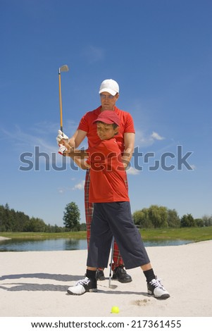 Mid adult man giving golf training to his son - stock photo