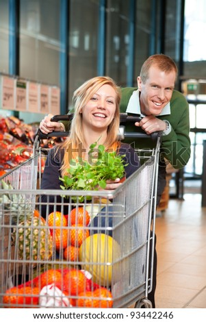 Mid adult man in playful mood holding shopping cart while woman sitting in it and looking at camera - stock photo