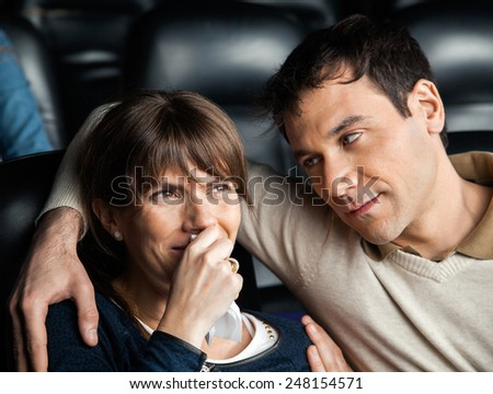 Mid adult man looking at woman crying while watching movie in cinema theater - stock photo