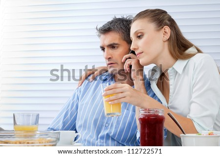 Mid adult man on call while woman beside him holding glass of orange juice