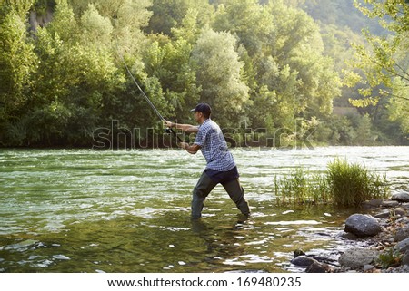 mid adult man on holidays on river, relaxing and fishing trout - stock photo