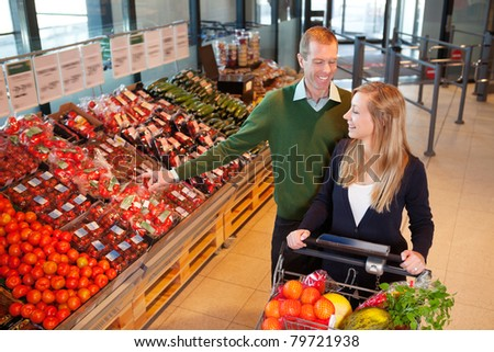 Mid adult man pointing at vegetables while shopping with wife in shopping store - stock photo