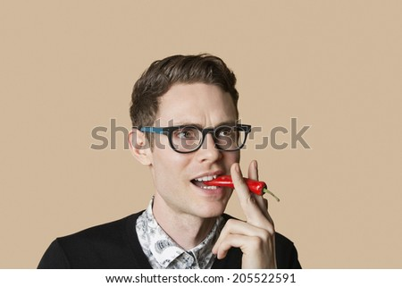 Mid adult man smoking red chili pepper over colored background - stock photo