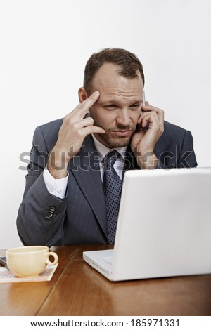 Mid Adult Man Using Laptop and Mobile Phone