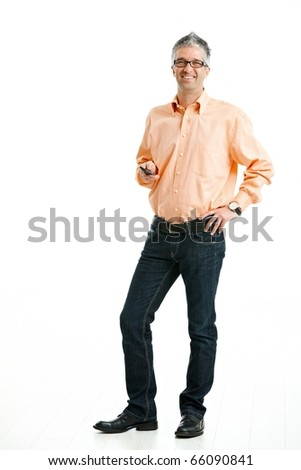 Mid-adult man wearing jeans and orange shirt standing and holding mobile phone. Isolated on white.?