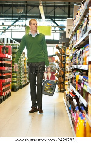 Mid adult man with shopping basket walking in grocery store and looking at products - stock photo