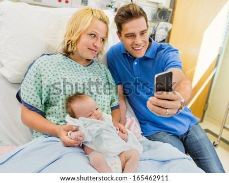 Mid adult man with woman and newborn babygirl taking selfportrait through mobile phone in hospital room - stock photo