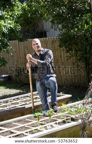 Mid-adult man working on vegetable garden in backyard - stock photo
