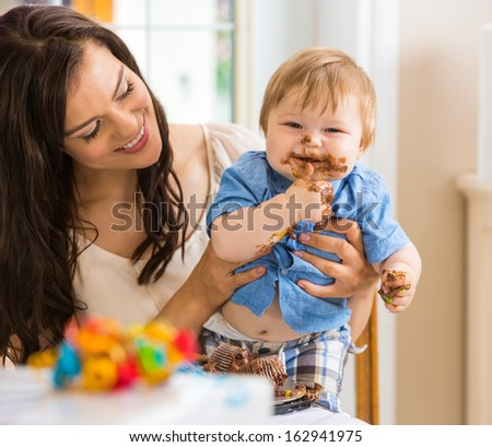 Mid adult mother holding baby boy eating cake with icing on face at birthday party - stock photo