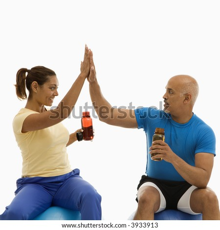 Mid adult multi-ethnic man and woman sitting on blue exercise balls giving each other the high five. - stock photo