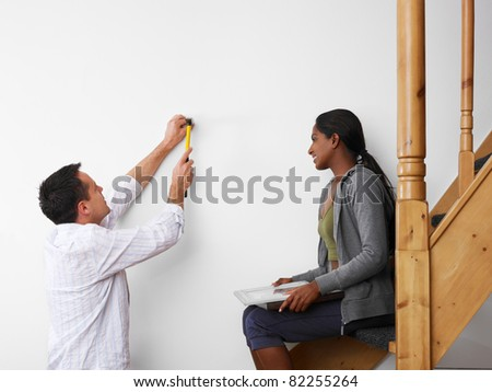 mid adult multiethnic couple using hammer to hang pictures to the wall and smiling. Copy space