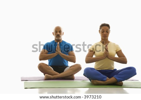 Mid adult multiethnic man and woman sitting in Namaste position on exercise mats with eyes closed and hands at heart center. - stock photo