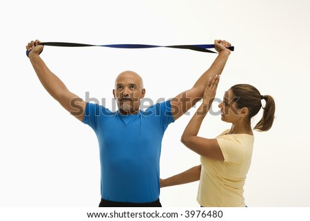 Mid adult multiethnic woman assisting mid adult multiethnic man with stretching band. - stock photo