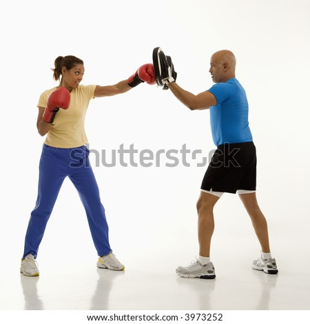 Mid adult multiethnic woman standing and punching focus mitts worn by multiethnic mid adult man. - stock photo