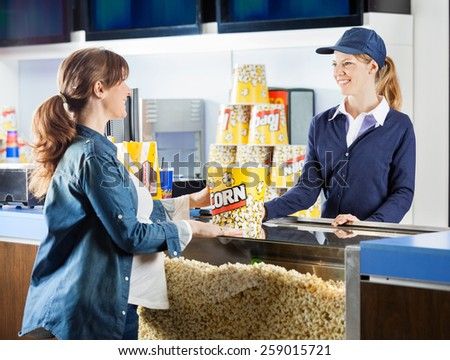 Mid adult pregnant woman buying popcorn from seller at cinema concession stand - stock photo