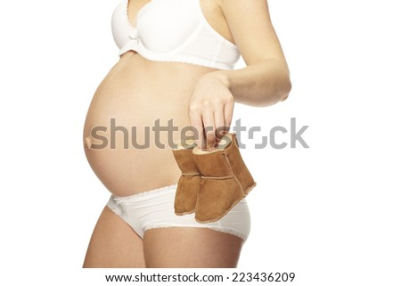 Mid adult pregnant woman in underwear holding bootees