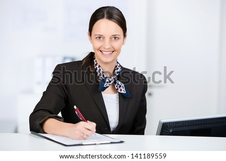 Mid adult receptionist signing check on clipboard at reception - stock photo