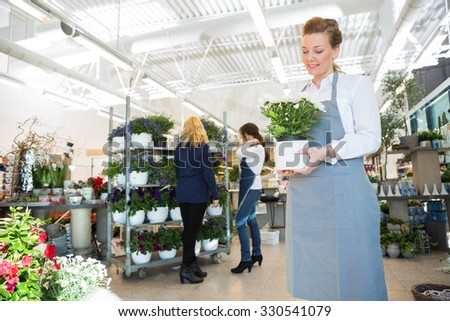 Mid adult salesgirl holding flower pot with customer and colleague in background at shop - stock photo