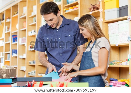 Mid adult saleswoman assisting male customer in choosing greeting card at shop - stock photo