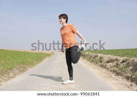 Mid adult woman doing stretching - stock photo