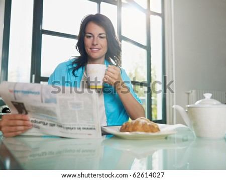 mid adult woman drinking coffee and reading news. Horizontal shape, copy space - stock photo