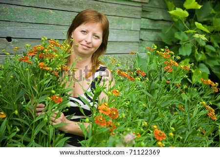Mid adult woman gardener with  Helenium in summer - stock photo