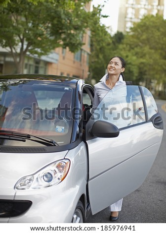 Mid-Adult Woman Getting Into Microcar