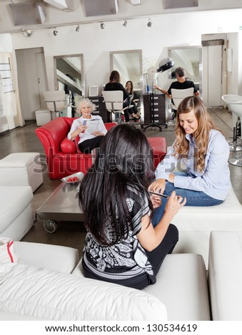 Mid adult woman having manicure with customers waiting in background at parlor - stock photo