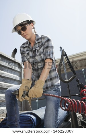 Mid adult woman holding a break hose of a logging truck - stock photo