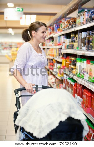 Mid adult woman holding baby stroller and looking at products in shopping centre - stock photo