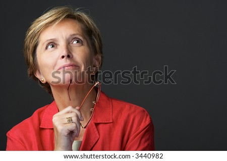 Mid adult woman holding glasses and looking up - stock photo