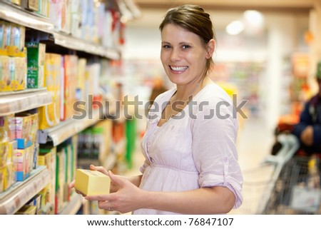 Mid adult woman holding product and looking at camera in shopping centre - stock photo