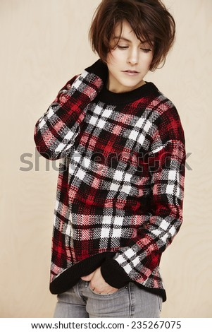 Mid adult woman in checked top looking down  - stock photo