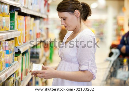 Mid adult woman looking at a product in shopping store with person in the background - stock photo
